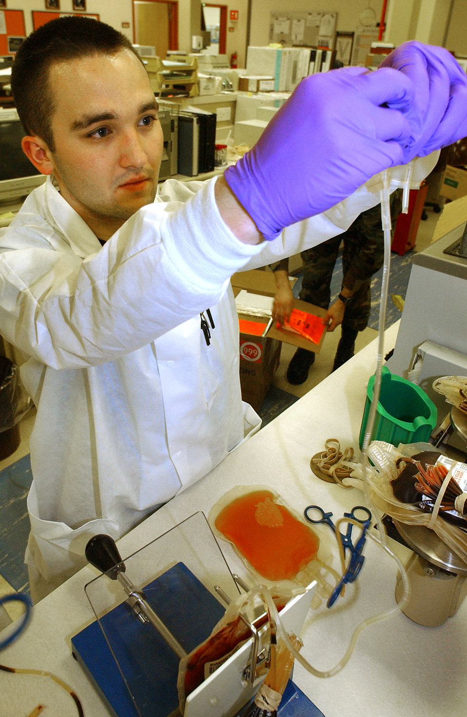 ROYAL AIR FORCE MILDENHALL, England -- Airman 1st Class Joshua Barnett squeezes a preservative solution into a bag of red blood cells so they are good for 42 days. The blood came from donors during a monthly blood drive. Airman Barnett is assigned to the 48th Medical Support Squadron.